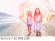 Купить «Mom with a small daughter walks along the beach with an umbrella on a sunny summer day.», фото № 32906236, снято 18 июля 2019 г. (c) Акиньшин Владимир / Фотобанк Лори