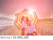 Купить «Mom with a small daughter walks along the beach with an umbrella on a sunny summer day.», фото № 32906240, снято 18 июля 2019 г. (c) Акиньшин Владимир / Фотобанк Лори