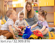 Купить «Kids play in kindergarten or daycare centre under the supervision of moms», фото № 32909816, снято 27 мая 2020 г. (c) Оксана Кузьмина / Фотобанк Лори