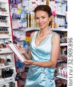 Купить «Woman with schemes choosing new nail polish in cosmetics store», фото № 32909896, снято 21 июня 2018 г. (c) Яков Филимонов / Фотобанк Лори