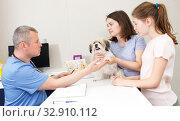 Купить «Worried family with puppy at veterinarian clinic», фото № 32910112, снято 3 мая 2018 г. (c) Яков Филимонов / Фотобанк Лори