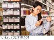 Fine Asian girl choosing pack of false eyelashes. Стоковое фото, фотограф Яков Филимонов / Фотобанк Лори