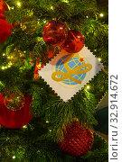 Купить «Украшения новогодней елки вечером: шары, светящиеся лампочки и белый флажок с изображением земного шара», фото № 32914672, снято 5 января 2020 г. (c) Наталья Николаева / Фотобанк Лори
