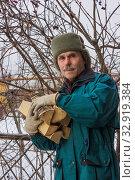 Купить «Пожилой мужчина с дровами. Зима», фото № 32919384, снято 11 января 2020 г. (c) Александр Романов / Фотобанк Лори