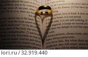 Golden wedding ring on bible book. Стоковое видео, видеограф Иван Михайлов / Фотобанк Лори