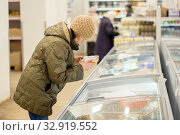 Купить «Russia Samara November 2019: A mature woman is standing in a store near the refrigerator, is holding a package with a semi-finished product in her hands and is looking at the price.», фото № 32919552, снято 13 ноября 2019 г. (c) Акиньшин Владимир / Фотобанк Лори