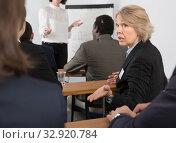 Купить «Discontent senior female turning to other participants», фото № 32920784, снято 12 февраля 2018 г. (c) Яков Филимонов / Фотобанк Лори