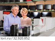 Купить «Adult married couple looking at and choose home appliances», фото № 32920852, снято 11 июля 2020 г. (c) Яков Филимонов / Фотобанк Лори