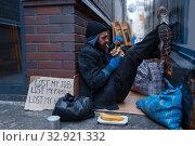 Bearded beggar eats burger on city street. Стоковое фото, фотограф Tryapitsyn Sergiy / Фотобанк Лори