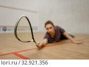 Female player with squash racket lies on the floor. Стоковое фото, фотограф Tryapitsyn Sergiy / Фотобанк Лори