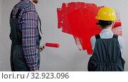 Купить «Apartment renovation - family painting walls in red color», видеоролик № 32923096, снято 3 июня 2020 г. (c) Константин Шишкин / Фотобанк Лори