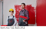 A little boy and his father painting walls - pulls out their rollers and the boy puts on helmet. Стоковое видео, видеограф Константин Шишкин / Фотобанк Лори