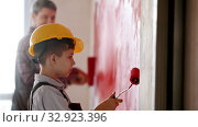 A little boy and his smiling father painting walls in red color om the new apartment - a boy wearing helmet. Стоковое видео, видеограф Константин Шишкин / Фотобанк Лори