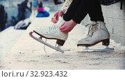 Купить «A young blonde woman tie up her figure skates before walking out on the rink», видеоролик № 32923432, снято 29 марта 2020 г. (c) Константин Шишкин / Фотобанк Лори