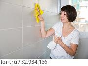 Купить «Woman cleaning tiled wall», фото № 32934136, снято 22 ноября 2018 г. (c) Яков Филимонов / Фотобанк Лори