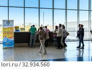 Купить «The Biblio Globus tour operator reception is in Larnaca International airport. Cyprus. Arrived Russian people check-in for get transfer to hotel after charter flight», фото № 32934560, снято 18 сентября 2013 г. (c) Кекяляйнен Андрей / Фотобанк Лори