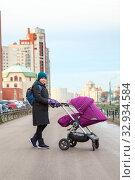 Happy young mother walks with a stroller and baby in a winter city. Стоковое фото, фотограф Кекяляйнен Андрей / Фотобанк Лори