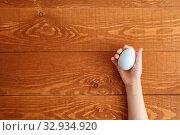 Купить «Painted Easter Egg In Hands Wooden Background», фото № 32934920, снято 25 марта 2019 г. (c) Иван Карпов / Фотобанк Лори