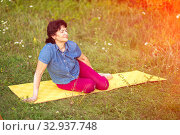 Купить «Beautiful mature women sits in Zelenaya Polyana on the mat after gymnastics on a summer day.», фото № 32937748, снято 9 августа 2019 г. (c) Акиньшин Владимир / Фотобанк Лори