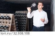 Proficient concentrated man holding glass of wine in cellar. Стоковое фото, фотограф Яков Филимонов / Фотобанк Лори