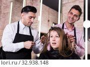 Купить «Brunette getting haircutting from two hairstylists», фото № 32938148, снято 5 марта 2018 г. (c) Яков Филимонов / Фотобанк Лори