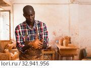 Купить «Craftsman moulding wet clay», фото № 32941956, снято 6 августа 2019 г. (c) Яков Филимонов / Фотобанк Лори