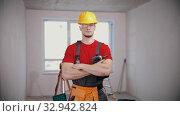 Купить «A young fit man worker in draft apartment holding instrument», фото № 32942824, снято 27 февраля 2020 г. (c) Константин Шишкин / Фотобанк Лори