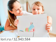 Kind mit Zeichnung vom Traumhaus als Wunsch für die Familie vor dem Umzug. Стоковое фото, фотограф Zoonar.com/Robert Kneschke / age Fotostock / Фотобанк Лори