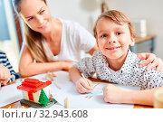 Mädchen beim Malen von Wunsch Haus zusammen mit Mutter vor dem Umzug. Стоковое фото, фотограф Zoonar.com/Robert Kneschke / age Fotostock / Фотобанк Лори