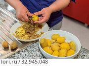 Köchin schält in der Küche frisch gekochte Kartoffeln - Nahaufnahme. Стоковое фото, фотограф Zoonar.com/Alfred Hofer / easy Fotostock / Фотобанк Лори