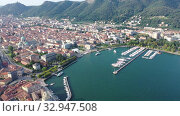 Купить «Picturesque view of city of Como on shore of Lake Como on background of mountain at sunny morning, Italy», видеоролик № 32947508, снято 1 сентября 2019 г. (c) Яков Филимонов / Фотобанк Лори