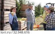 Купить «Cheerful team eating apples after harvesting in the garden», видеоролик № 32948616, снято 28 сентября 2019 г. (c) Яков Филимонов / Фотобанк Лори