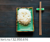 Купить «Top view of portion of boiled rice on green plate and chopsticks on rest on brown table with copyspace», фото № 32950616, снято 25 мая 2020 г. (c) easy Fotostock / Фотобанк Лори