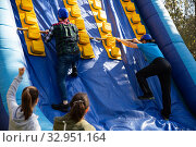 Купить «Friends climbing on inflatable slide in amusement park», фото № 32951164, снято 20 февраля 2020 г. (c) Яков Филимонов / Фотобанк Лори
