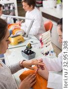 Купить «Manicurists giving manicure», фото № 32951308, снято 28 апреля 2017 г. (c) Яков Филимонов / Фотобанк Лори