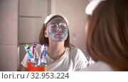 A young woman washes off a grey mask from the face. Стоковое видео, видеограф Константин Шишкин / Фотобанк Лори