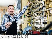 male worker showing key he made in repair workshop. Стоковое фото, фотограф Яков Филимонов / Фотобанк Лори
