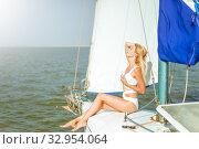 Купить «Young beautiful slim sexy girl in bikini and pareo is resting on cruise on a private sailing yacht», фото № 32954064, снято 25 июля 2017 г. (c) katalinks / Фотобанк Лори