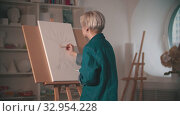 A young woman artist starts painting her sketch in beige color in the art studio. Стоковое видео, видеограф Константин Шишкин / Фотобанк Лори