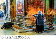 MTSKHETA, GEORGIA - OCT 25, 2018: Woman praying in Svetitskhoveli Cathedral in the historic town of Mtskheta, Georgia. Стоковое фото, фотограф Zoonar.com/monticello / age Fotostock / Фотобанк Лори