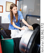 Купить «Woman in uniform taking out clothes from washing machine at laundry», фото № 32962172, снято 22 января 2019 г. (c) Яков Филимонов / Фотобанк Лори