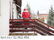 One woman dressed red jacket stading on porch of her townhouse at winter season. Стоковое фото, фотограф Кекяляйнен Андрей / Фотобанк Лори