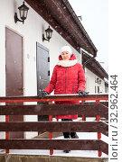 Купить «A woman in red jacket is standing on the porch against double townhouse doors. Winter season with snowfall», фото № 32962464, снято 4 января 2020 г. (c) Кекяляйнен Андрей / Фотобанк Лори
