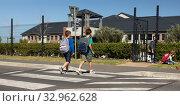 Купить «Two schoolboys crossing the road on a pedestrian crossing», фото № 32962628, снято 1 декабря 2019 г. (c) Wavebreak Media / Фотобанк Лори