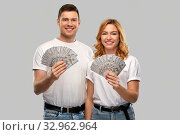 Купить «happy couple in white t-shirts with dollar money», фото № 32962964, снято 6 октября 2019 г. (c) Syda Productions / Фотобанк Лори