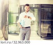 Купить «man with folder looking at wristwatch on street», фото № 32963000, снято 21 августа 2016 г. (c) Syda Productions / Фотобанк Лори