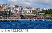 Tenerife, Spain - October 15, 2019: Waterside distant view Los Cristianos coastline, people enjoy warm Atlantic Ocean pretty beach, touristic town, situated on south coast of Canary Islands, Spain. Редакционное фото, фотограф Alexander Tihonovs / Фотобанк Лори