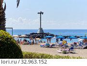 Tenerife, Spain - October 13, 2019: People sunbathing on sandy beach of Playa de los Cristianos, enjoy warm Atlantic Ocean waters, Tenerife, Canary Islands, Spain. Редакционное фото, фотограф Alexander Tihonovs / Фотобанк Лори