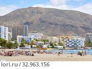 People sunbathing on sandy beach of Playa de los Cristianos, Tenerife, Canary Islands, Spain (2019 год). Редакционное фото, фотограф Alexander Tihonovs / Фотобанк Лори