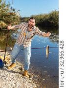 Купить «Adult man standing near river and pulling fish expressing emotions of dedication», фото № 32966428, снято 15 марта 2019 г. (c) Яков Филимонов / Фотобанк Лори
